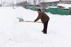 Человек очищает лопаткоулавливатель снега Стоковые Фотографии RF