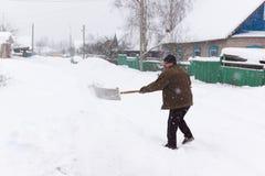 Человек очищает лопаткоулавливатель снега Стоковые Фото