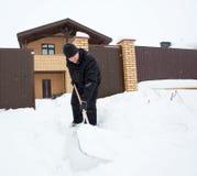 Человек очищает снег вокруг дома Стоковое Изображение