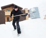 Человек очищает снег вокруг дома Стоковая Фотография RF