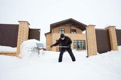 Человек очищает снег вокруг дома Стоковые Изображения RF