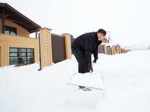 Человек очищает снег вокруг дома Стоковая Фотография