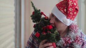 Человек одевает красивую маленькую накаляя рождественскую елку видеоматериал