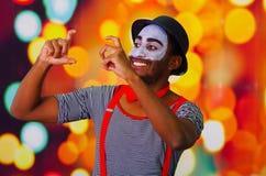 Человек пантомимы нося лицевую краску представляя для камеры, используя язык жестов рук взаимодействуя, расплывчатая предпосылка  Стоковое Фото