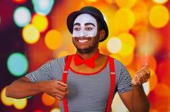 Человек пантомимы нося лицевую краску представляя для камеры, используя язык жестов рук взаимодействуя, расплывчатая предпосылка  Стоковое Изображение