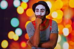 Человек пантомимы нося лицевую краску представляя для камеры, используя язык жестов рук взаимодействуя, расплывчатая предпосылка  Стоковые Фотографии RF