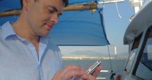 Человек печатает на его smartphone пока он плавает на шлюпке в дне лета солнечном видеоматериал