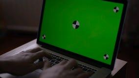 Человек печатает на компьтер-книжке на его столе Зеленый экран для вашего изготовленного на заказ содержания экрана сток-видео