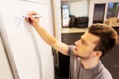 Человек писать номера к whiteboard в спортзале Стоковые Изображения RF