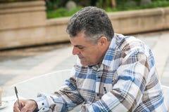 Человек писать outdoors Стоковое Фото