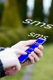 Человек пишет sms от мобильного телефона Стоковые Фото