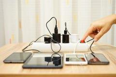 Человек поворачивает переходники силы для мобильных телефонов и таблетки Стоковые Фотографии RF