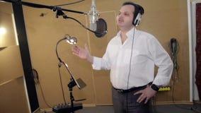 Человек поет в наушниках перед микрофоном Gesticulation руки студия сток-видео