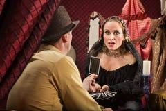 Человек показывает женщине карточку Tarot стоковые фото