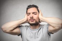 Человек покрывая его уши стоковая фотография rf