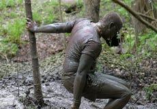 Человек покрытый с склонностью грязи на дереве Стоковое Изображение