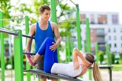 Человек помогает женщине с тренировкой Стоковое фото RF