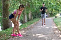 Человек помогает к женщине с раненым коленом на деятельности при спорта стоковые изображения