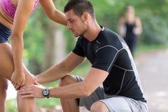 Человек помогает к женщине с раненым коленом на деятельности при спорта стоковое фото rf