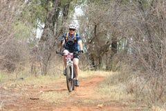 Человек постаретый серединой наслаждаясь outdoors ездой на гонке горного велосипеда Стоковое Фото