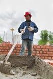 Человек построителя работает с лопаткоулавливателем на строительной площадке Стоковые Изображения RF
