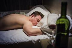 Человек похмелья в кровати на ноче стоковая фотография