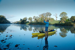 Человек подготавливая пойти рыбная ловля каяка стоковые фотографии rf