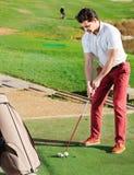 Человек подготавливая ударить шарик на поле для гольфа Стоковое Изображение