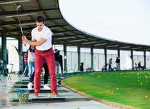 Человек подготавливая ударить шарик на поле для гольфа Стоковые Фото