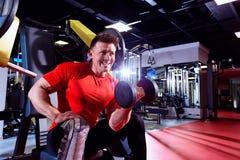 Человек поднимает гантели в спортзале Стоковая Фотография RF