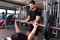 Человек поднятия тяжестей жима лёжа с личным тренером стоковое изображение