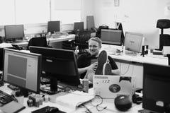 Человек положил ноги вверх на таблицу работы во время периода отдыха на офисе Стоковые Фото