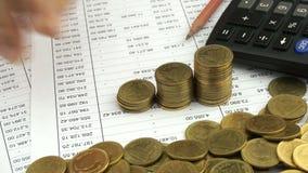 Человек подсчитывая золотые монетки на учете финансов сток-видео