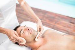Человек получая лицевой массаж от masseur стоковая фотография