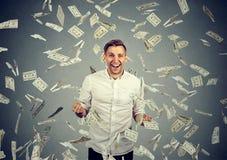 Человек празднует успех под дождем денег падая вниз долларовые банкноты стоковые изображения