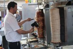 Человек прерывает куски kebap на стойке улицы Стоковые Фото