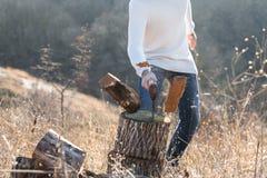 Человек прерывая древесину с осью Стоковое Изображение