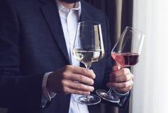 Человек предлагая 2 высокорослых стекла с вином Стоковые Изображения