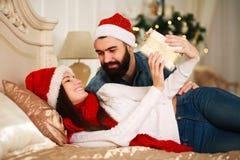 Человек представляет подарок Нового Года девушки, пару рождества в кровати Стоковая Фотография RF