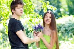 Человек представляя голубые цветки к женщине Стоковые Фотографии RF