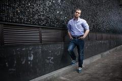 Человек представляя около черной стены Стоковое Изображение