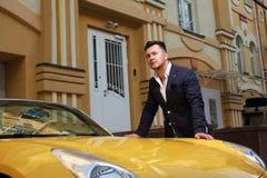 Человек представляя с обратимое sportcar Стоковые Фото