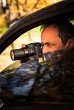 Человек прикрытия спрятанный в автомобиле принимает фото стоковая фотография