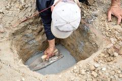 Человек прикладывая цемент в отверстии почвы Стоковое фото RF