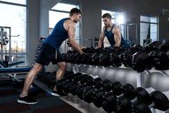 Человек принимает гантели в спортзале Стоковая Фотография RF