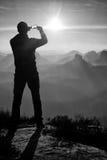 Человек принимает фото телефона Мечтательные горы fogy пока восход солнца Стоковые Фотографии RF