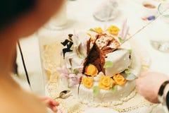 Человек принимает часть свадебного пирога пока невеста стоит с spoo стоковые фотографии rf