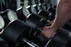 Человек принимая гантели для работать на спортзал Стоковое Изображение
