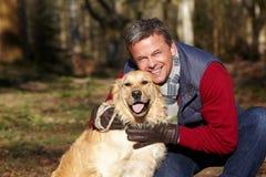 Человек принимая собаку на прогулке через древесины осени стоковые изображения rf