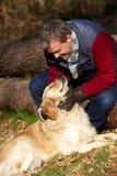Человек принимая собаку на прогулке через древесины осени Стоковое Изображение